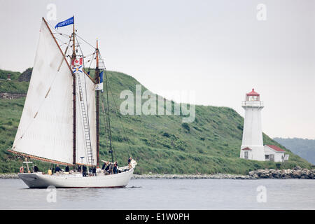Tall ship Bowdoin sails past the lighthouse on George's Island in Halifax Harbour during the Parade Sail conclusion - Stock Photo