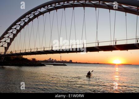 Young man paddling kayak under Humber River Arch Bridge on Lake Ontario, Toronto, Ontario, Canada. - Stock Photo