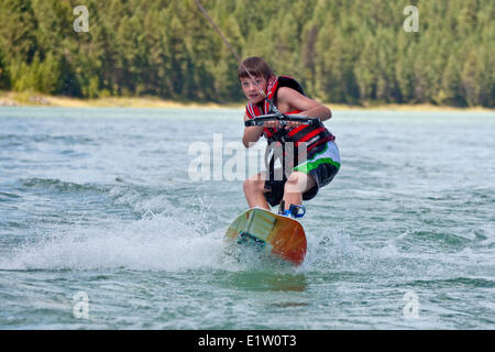Young boy wakeboarding on Lake Koocanusa, East Kootenays, BC, Canada - Stock Photo