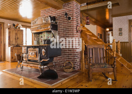Old Legare's Rural antique wood stove in the living room a Canadiana cottage style fieldstone residential home built - Stock Photo