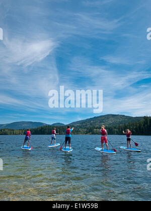 A Family Practises Stand Up Paddling On Heffley Lake Near