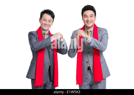 Businessmen offering traditional Chinese New Year greeting - Stock Photo