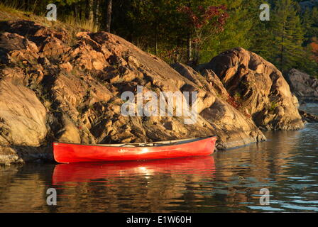 Red Canoe along a rocky shore on George Lake, Kilarney provincial park, Ontario - Stock Photo