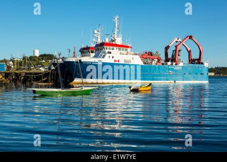 Small wooden boats and fishing boat, Lunenburg waterfront, Nova Scotia, Canada - Stock Photo