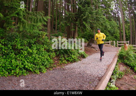 Running and hiking on the trail around Sasamat Lake, Belcarra Regional Park, Port Moody, British Columbia, Canada - Stock Photo