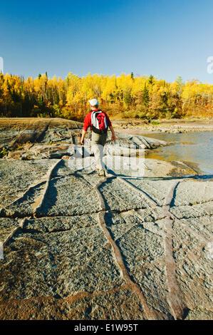 Hiking on precambrian shield rock along the Winnipeg River, near Seven Sisters, Manitoba, Canada - Stock Photo
