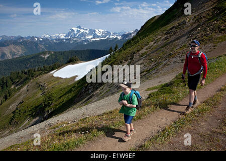 Young Boy Father Hiking on Skyline Divide Trail Mt Shuksan in Distance Mount Baker Wilderness Area Washington State - Stock Photo