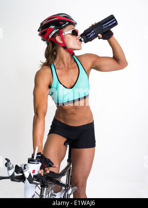 Muscular toned athletic woman  - cyclist / triathlete on racing bike drinking from water bottle - Stock Photo