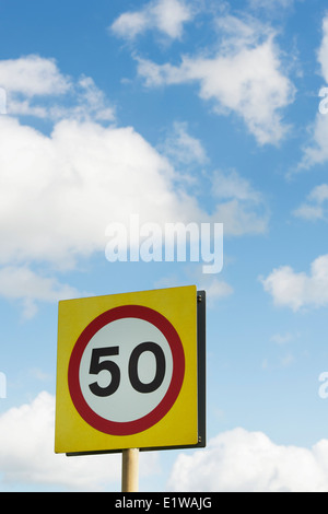 50 MPH Speed limit road sign against blue cloudy sky. England - Stock Photo