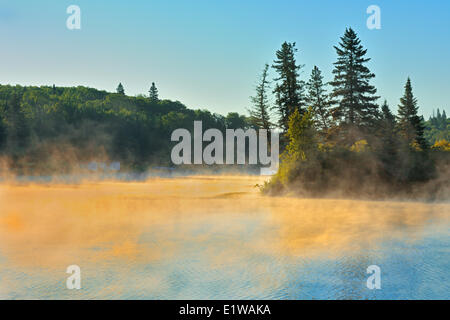 Fog rising off the Winnipeg River at sunrise in boreal forest, Lac du Bonnet, Manitoba, Canada - Stock Photo