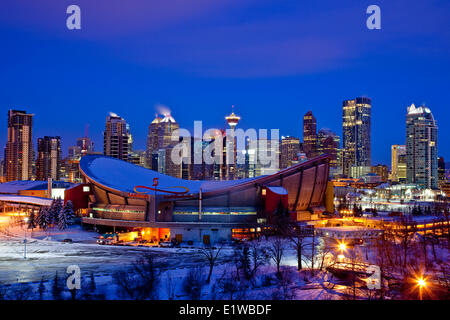 Calgary skyline at night in winter with Scotiabank Saddledome in foreground, Calgary Alberta, Canada. - Stock Photo