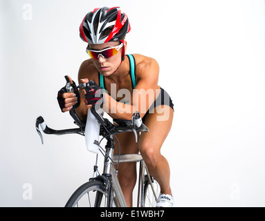 Muscular toned athletic woman - cyclist / triathlete on racing bike - Stock Photo