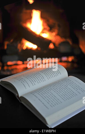 Open book by a fireplace - Stock Photo