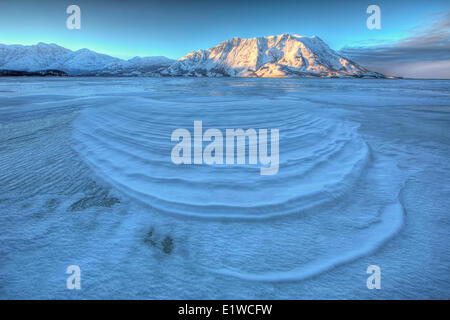 Wind blown snow create interesting patterns on the frozen surface Kluane Lake Yukon. Sheep mountain is seen in the - Stock Photo