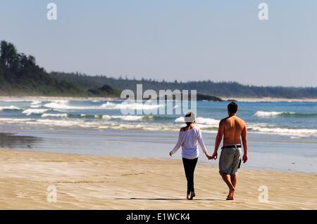 A young couple walking hand in hand on Long Beach in the Pacific Rim National Park near Tofino, BC. - Stock Photo