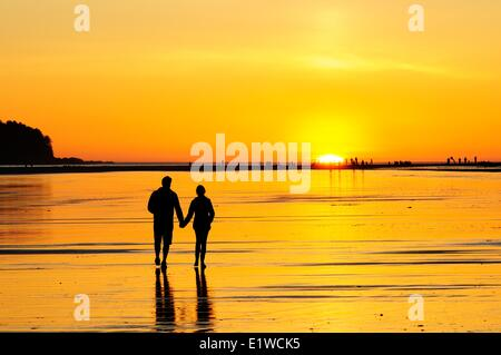 Young couple at sunset walking along Chesterman Beach near Tofino, BC. - Stock Photo