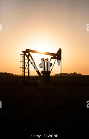 Oil pumpjack silhouetted against the rising sun in Southern Manitoba, Canada - Stock Photo