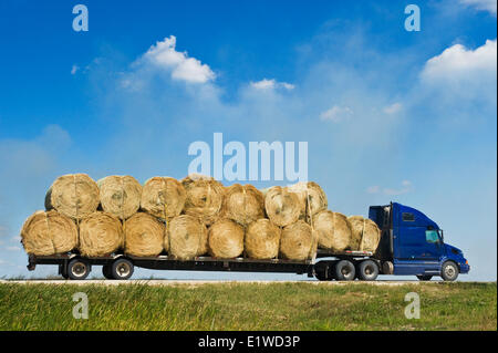 a truck loaded with round hay bales on a country road ,  Manitoba, Canada - Stock Photo