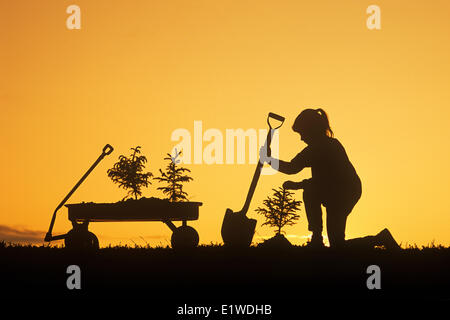 a girl holding a shovel, examines a spruce tree she has just planted, Winnipeg, Manitoba, Canada - Stock Photo