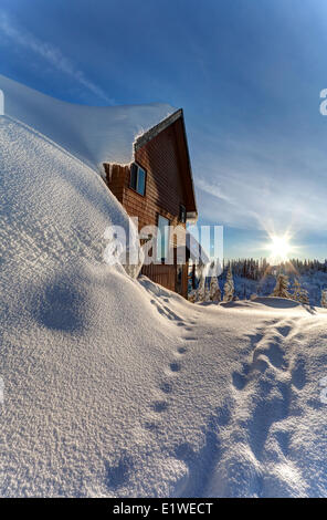 A ski chalet blanketed in deep snow is a familiar site up at Mt. Washington's small village loacted near the ski - Stock Photo