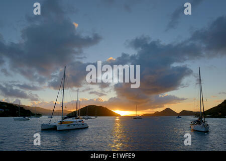 Catamarans and sailboats at anchor in Soper's Hole at sunset, West End, Tortola, British Virgin Islands - Stock Photo