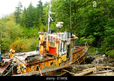 An long-retired fishing boat collects moss on the shores of North Bentinck Arm, Bella Coola, British Columbia - Stock Photo
