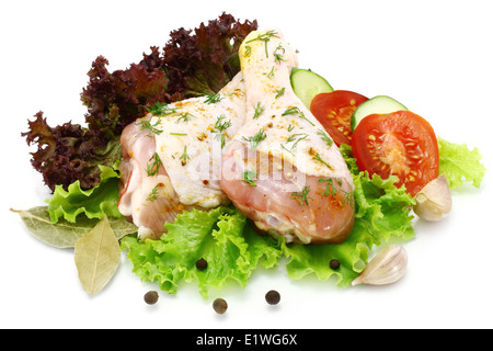 Raw chicken legs with vegetables on a white background - Stock Photo