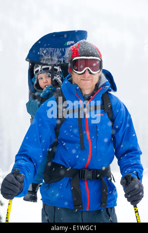 A man and his young son enjoy a walk in the snow, Monashee Mountains, British Columbia - Stock Photo