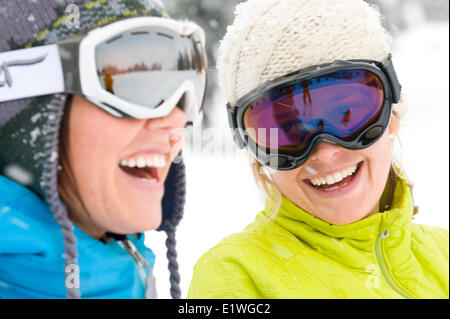 Two young women laugh while on a ski trip in the Monashee Mountains, British Columbia - Stock Photo