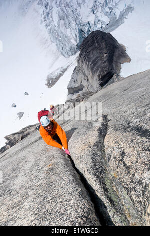 A pair of rock climbers ascend Surf's Up, a route on Snowpatch Spire in the Bugaboos, British Columbia - Stock Photo