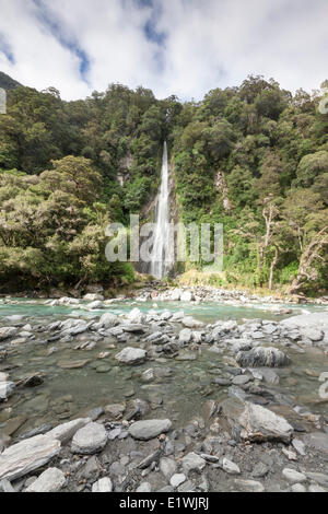 Thunder Creek Falls tumbles into the Haast River in Mount Aspiring National Park, New Zealand - Stock Photo