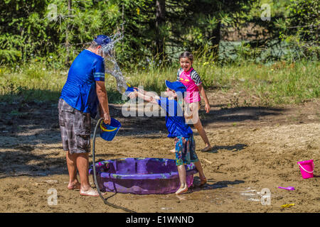 Adult and children in a playfull water fight , on a hot, sunny summer day. Cranbrook, British Columbia, Canada. - Stock Photo
