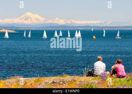 A couple watch laser sailboats racing off Cattle Point in Oak Bay in Victoria, BC. - Stock Photo