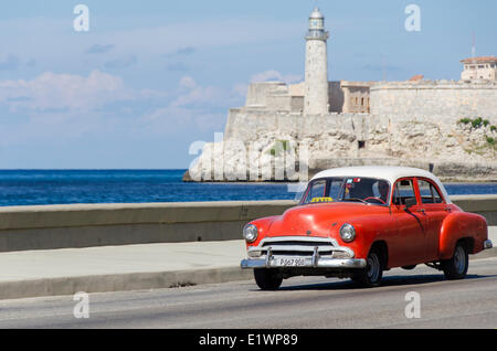 Vintage american cars alomg the Malecon, behind is Morro Castle, a picturesque fortress guarding the entrance to - Stock Photo