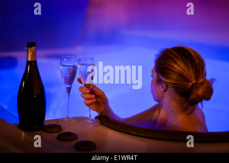 Attractive women relaxing in hot tube and drinking champagne on New Years Eve - Stock Photo