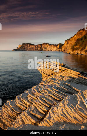 Lobster boats checking their traps by the cliffs of Cap-Bon-Ami in Forillon National Park, Quebec, Canada - Stock Photo