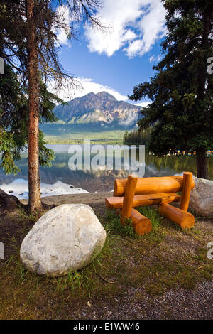 Middle age male sitting on bench at Pyramid Lake looking at Pyramid Mountain, Jasper National Park, Alberta, Canada. - Stock Photo
