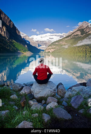 Middle age male meditating on rock at Lake Louise, Alberta, Canada. - Stock Photo