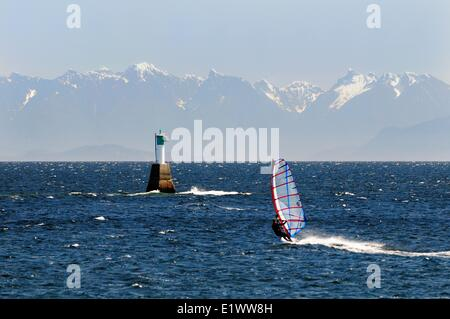 A windsurfer heads towards a marine marker in the Strait of Georgia near Pipers Lagoon in Nanaimo, BC.  The coastal - Stock Photo