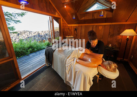 A client receives a back massage at the Ancient Cedars seaside Spa while staying at the luxurious Wickaninnish Inn - Stock Photo