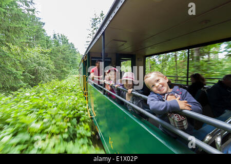 Young children enjoy the open air passenger cars on the Alberni Pacific Steam Train enroute Port Alberni to the - Stock Photo