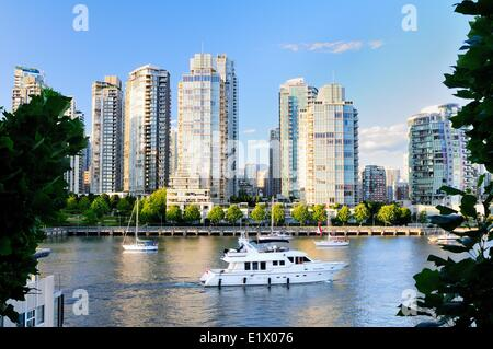 Boats and yachts in False Creek with the False Creek skyline in the background, in Vancouver, BC. - Stock Photo