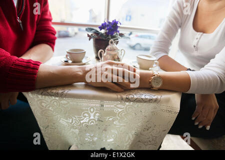 Midsection of couple holding hands in cafe - Stock Photo