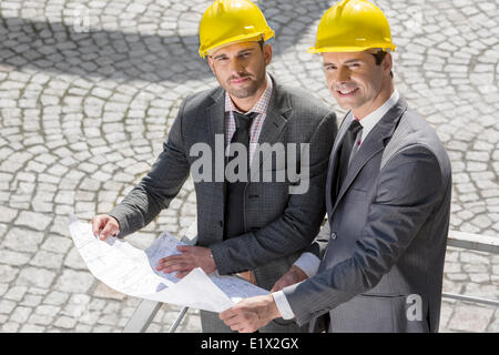 Portrait of confident young businessmen in hard hats examining blueprint outdoors - Stock Photo
