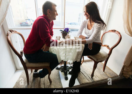 Full length of loving young couple holding hands and looking at each other in cafe - Stock Photo