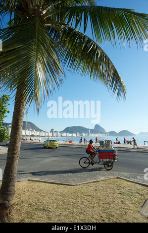 RIO DE JANEIRO, BRAZIL - FEBRUARY 03, 2014: Brazilian man delivering cooler and chairs to beach kiosk on a tricycle - Stock Photo