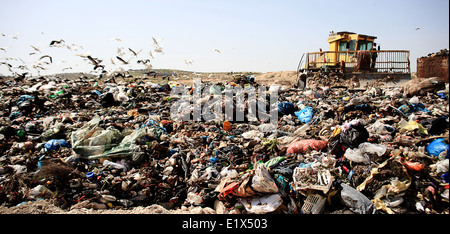 A bulldozer is arranging solid waste for a landfill site. - Stock Photo