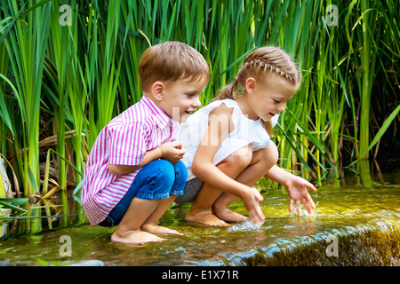 boy and girl sitting in water near small waterfall, wet feet - Stock Photo