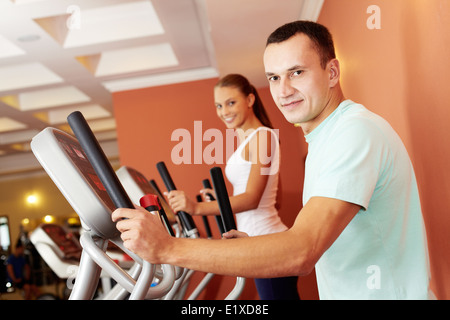 Portrait of young man training on special sport equipment in gym - Stock Photo