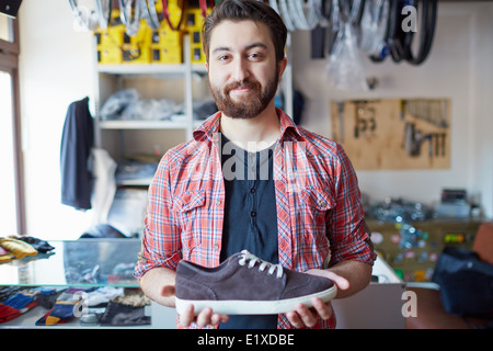 Portrait of a handsome man selling footwear in sports shop - Stock Photo